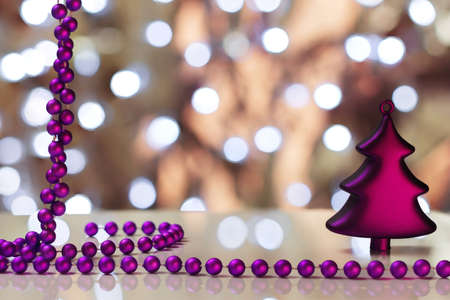 magentas: Christmas decoration from magentas Christmas tree-toy and beads on a background with boken