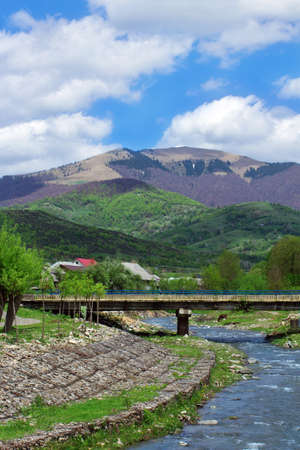 crankle: landscape consisting of a river, paving stone and bridge on the foreground  and Carpathians mountains with green trees in the middle of the image and blue sky with white clouds on the background