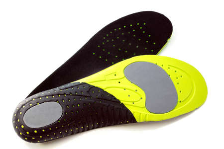 Orthopedic insoles for athletic shoes on white background