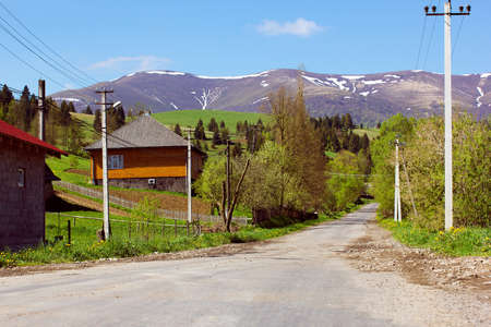 road position: landscape consist of asphalted road with houses on the foreground and mountains with various green trees in the middle ground and the tops of the mountains, with thawing snow and cloud in the blue sky in the background Stock Photo