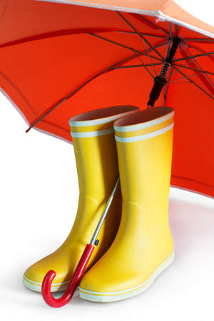 zapatos de seguridad: Pair of yellow rubber boots with an open orange umbrella on a white background