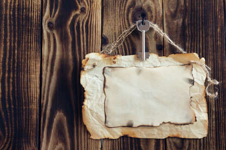 key hanging on a nail and scorched paper hanging on a rope on a wooden brown background