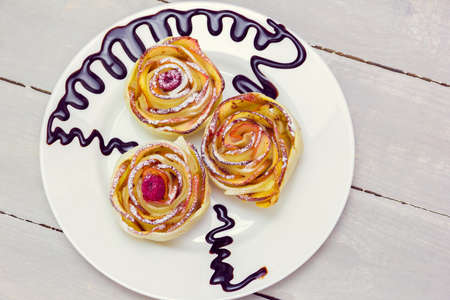 three apple muffins with raspberries in the center, drizzled with chocolate sauce leaving a zigzag trail on a white plate on a wooden grey background
