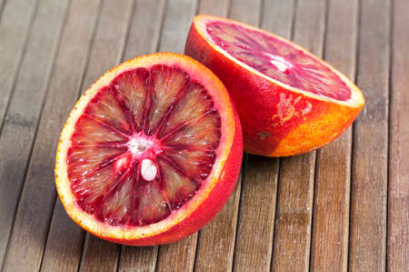 the juicy Blood orange cut in half on a wooden striped brown background