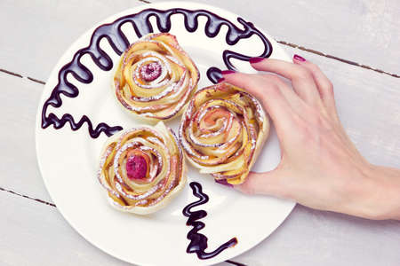 strudel: womans hand take one of three apple muffins with raspberries in the center, drizzled with chocolate sauce leaving a zigzag trail on a white plate on a wooden grey background Stock Photo