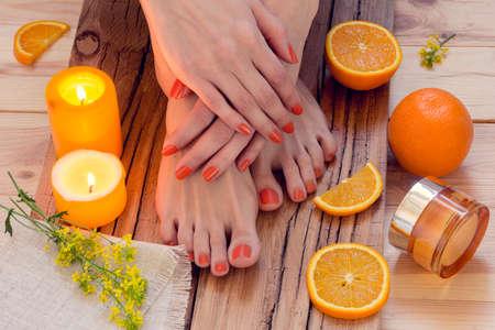 スパ。美容女性のスキンケア手と足にキャンドル、オレンジ、クリームと花