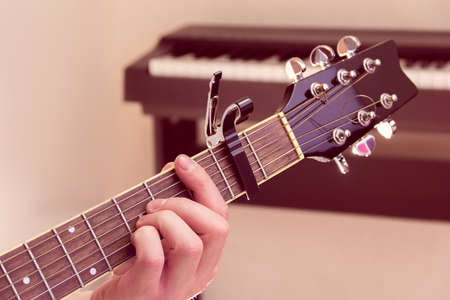 Mans hand plays the guitar with piano on a background Stock Photo