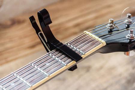 Black capo on a guitar on a wooden background Foto de archivo