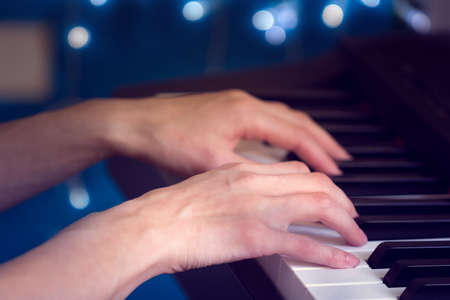 womens hands playing the piano on a blue bokeh background Stock Photo