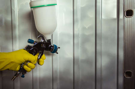 pulverizer in a mans hand with yellow glove on a metal background