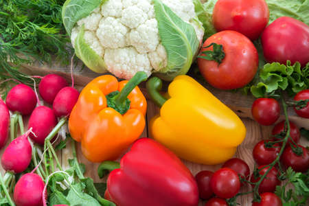 Different vegetables as a tomatoes, cauliflower, peppers, radishes, cherry tomatoes on a wooden background
