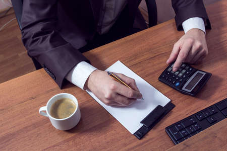 businessman doing calculations, writing down and drink coffee Stok Fotoğraf