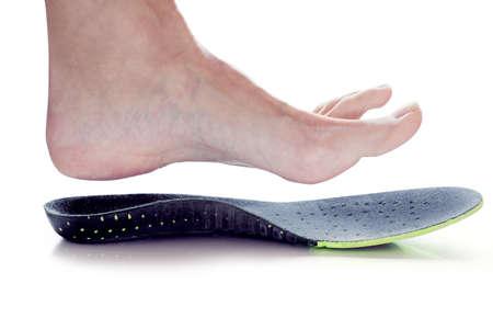 Plantilla ortopédica y pierna femenina sobre ella