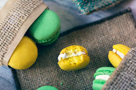 yellow and green macaroons in boxes packed with burlap. One of this is a bitten off