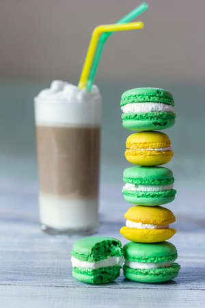 macaroons are laid by a stairs and latte in a glass Stock Photo
