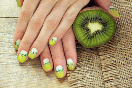 Kiwi and skin care of a beauty female hands with green and white moon nail art manicure on a sackcloth and wooden background 版權商用圖片