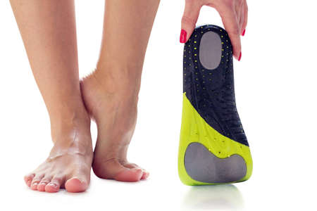 vrouwelijke voeten staan op hun tenen en orthopedische binnenzool in de hand