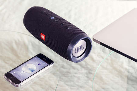 portable speaker JBL Ð¡harge 3 on a glass table produces music from the iPhone - January 16, 2018 新聞圖片