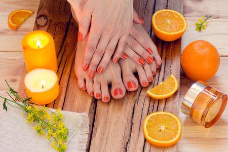SPA. Huidverzorging van een vrouwelijke schoonheid handen en voeten met kaarsen, sinaasappels, room en bloemen
