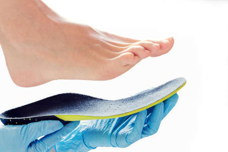 Hands in rubber gloves hold an orthopedic insole 스톡 콘텐츠 - 97037998