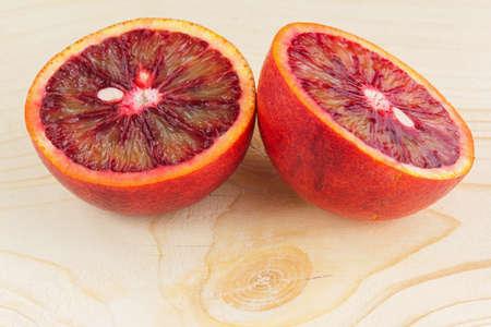 the juicy Sicilian orange cut in half on a wooden light background