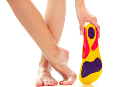 orthopedic insole in the hand and female feet stand on tiptoe
