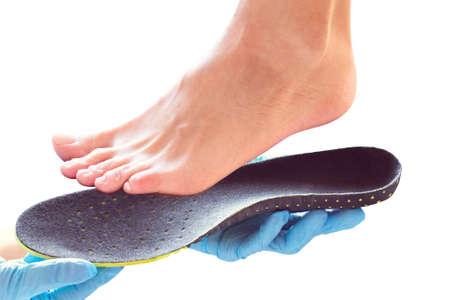 Las manos con guantes de goma sostienen una plantilla ortopédica