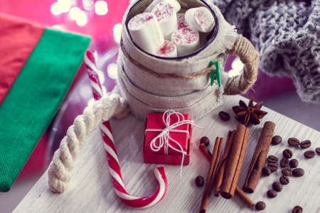 Warm winter mug with marshmallow, lollipop and gift. Cozy winter still life