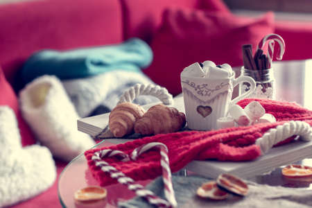 cozy winter still life, consist of, cup of coffee, marshmallow, croissants, striped lollipop on the foreground and fur shoes with  sweaters in the home interior living room