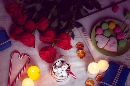 Candlelight dinner with red roses and gifts Stock Photo