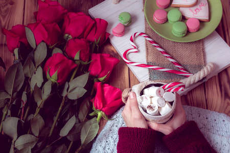 womens hands with coffee and red roses with heart of striped lollipop