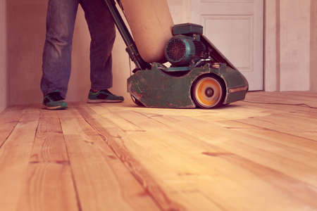 carpenter polishes a wooden floor by electric grinding wood machine in a room