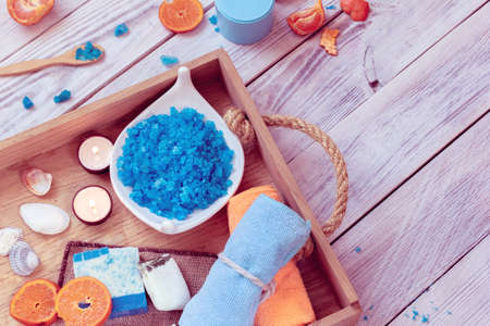 SPA consist from towels, blue sea salt, candles and tangerines in a wooden tray Stockfoto