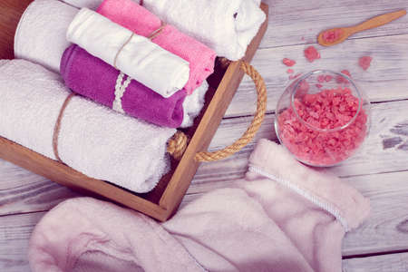 SPA consist from bathrobe, crumbled pink sea salt and towels in a wooden tray