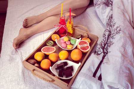 breakfast from different fruits and beverage to bed and female legs protruding from under the blanket