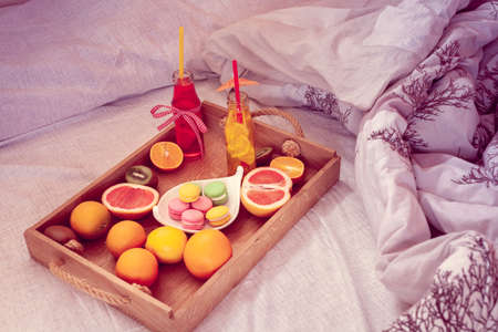 breakfast from different fruits and beverage to bed