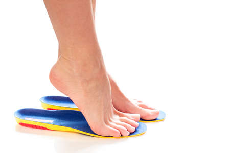 female feet stand tiptoe in orthopedic insoles