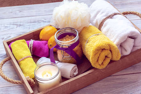 SPA consist from yellow sea salt, lemons and other accessories for bath in a wooden tray