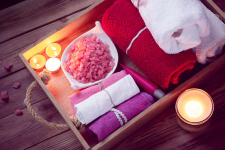 SPA consist from colorful towels, pink sea salt and candles on a wooden tray. Picture in Low-key lighting Stock Photo