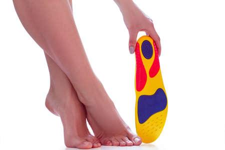 semelle orthopédique dans la main et les pieds féminins se tiennent sur la pointe des pieds