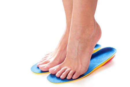 les pieds féminins se tiennent sur la pointe des pieds dans des semelles orthopédiques