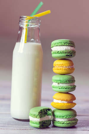 macaroons are laid by a stairs and milk in a bottle