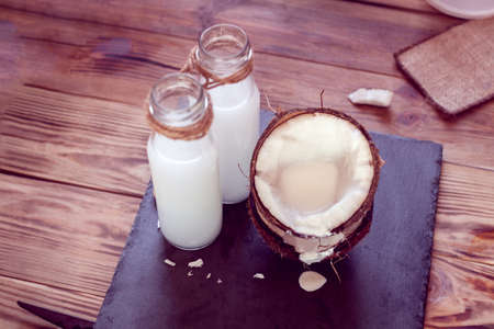 two half of  coconut and two bottles of coconut milk on a black background Stock Photo