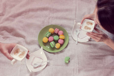 couple breakfast in bed with coffee and macaroons