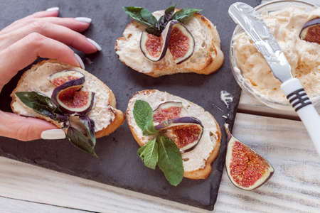 female  hand takes a toaster smeared by ricotta with figs