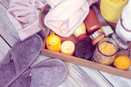 SPA consist from grey slippers, bathrobe, towels and other accessories for bath in a wooden tray