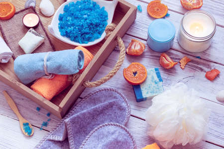 SPA consist from towels, blue sea salt, candles in a wooden tray and tangerines Stock Photo