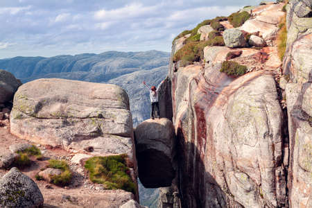 a girl stands with her hands up on Kjerag stone