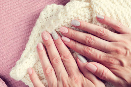 knitted texture manicure on nails from pink and gray colors with white scarf