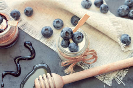 two jars of yogurt with blueberries, honey and chocolate